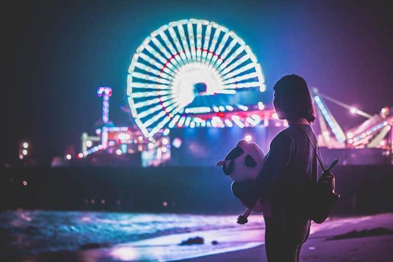 Das Mädchen beobachtet nachts den Vergnügungspark