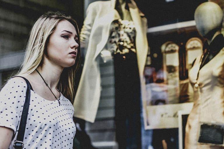 Das Mädchen geht am Boutique-Fenster vorbei