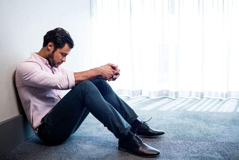 Deprimierter Geschäftsmann, der gegen eine Wand sitzt und im Studio nach unten schaut