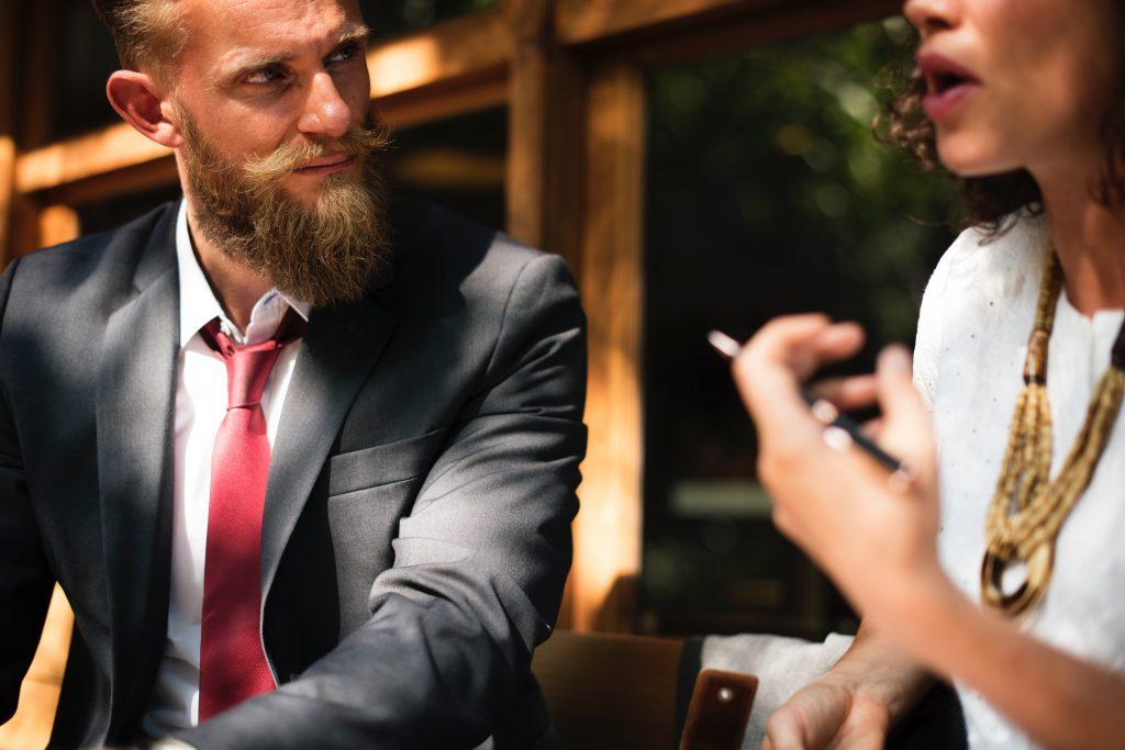 Der Mann mit dem Bart hört aufmerksam auf die sprechende Frau