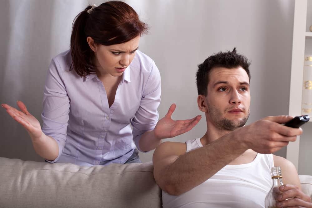 Der Mann sitzt auf der Couch und ignoriert die wütende Frau