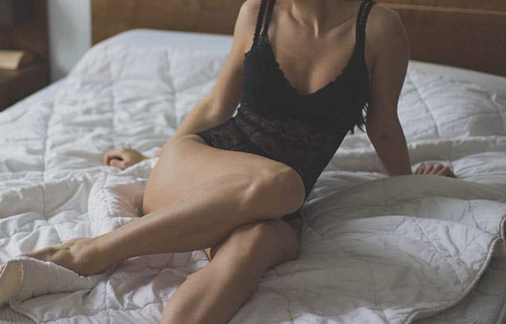 Frau in sexy Dessous sitzt auf dem Bett