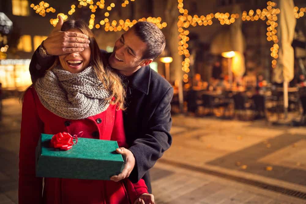 Ein Mann hält die Augen bedeckt, damit seine Frau das Geschenk nicht sieht