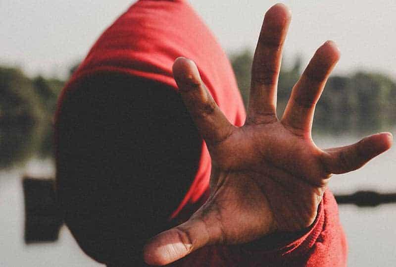 Ein Mann in einem roten Sweatshirt steht draußen und hält eine erhobene Hand auf Kopfhöhe