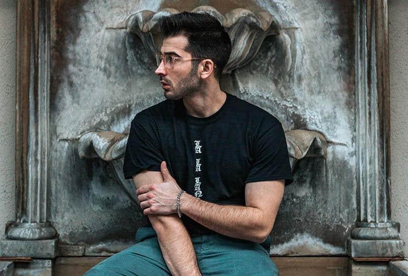 Ein Mann in einem schwarzen T-Shirt mit Brille sitzt neben einem Brunnen