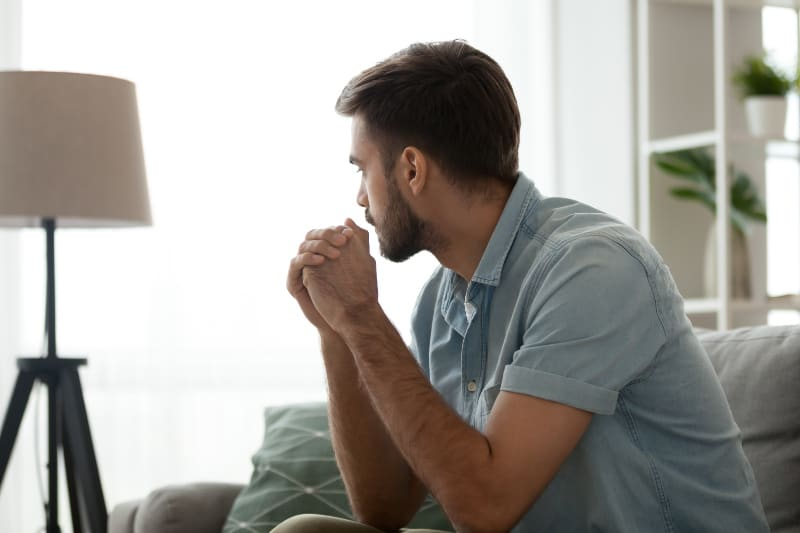Ein Mann sitzt auf einer Couch und ist voller Gedanken