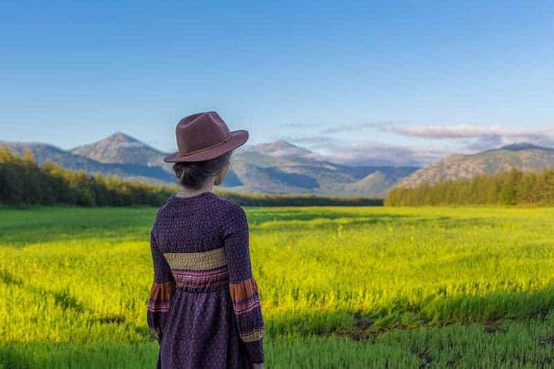 Eine Frau mit einem Hut auf dem Kopf steht auf einem Feld