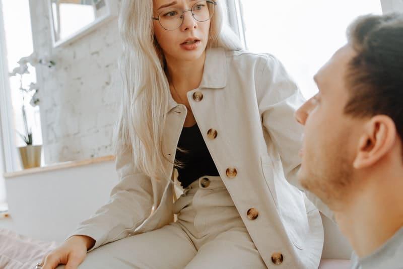 Eine besorgte Frau mit Brille sitzt auf der Couch und spricht mit ihrem Mann