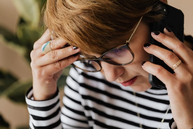Eine besorgte und traurige Frau, die jemanden über ihr Handy anruft