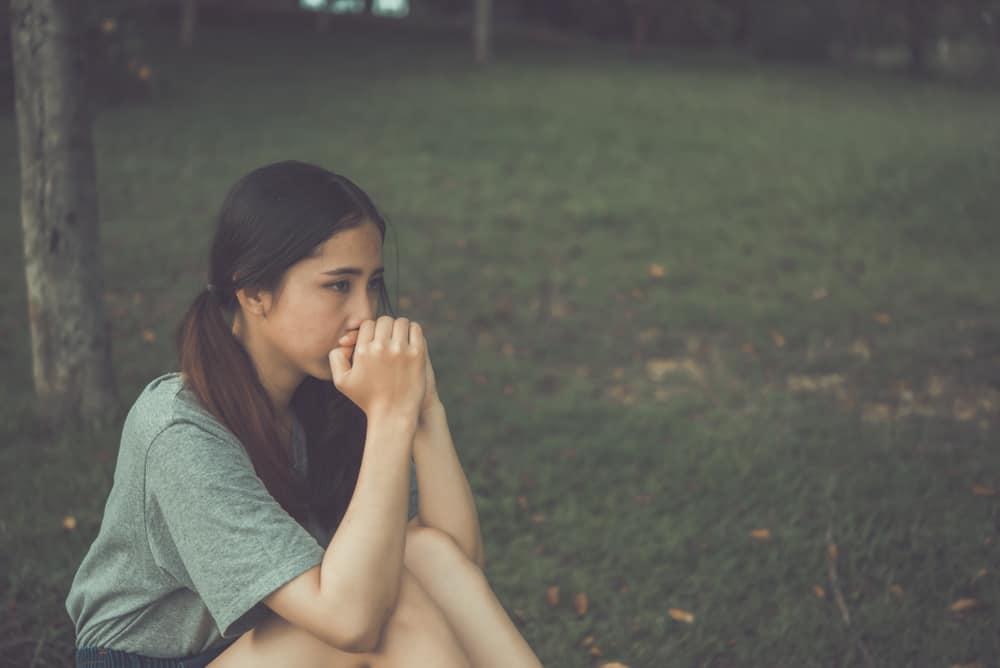 Eine einsame besorgte asiatische Frau sitzt im Gras