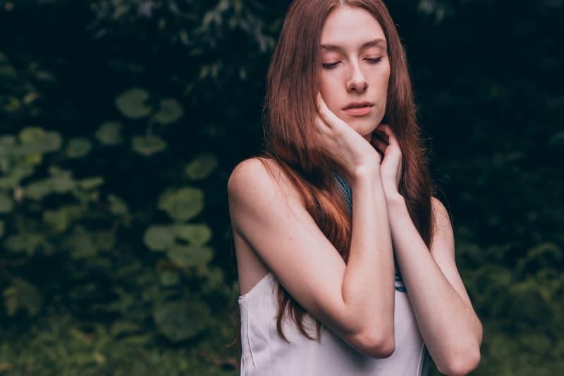 Eine rothaarige traurige Frau in einem weißen Gürtel steht im Wald