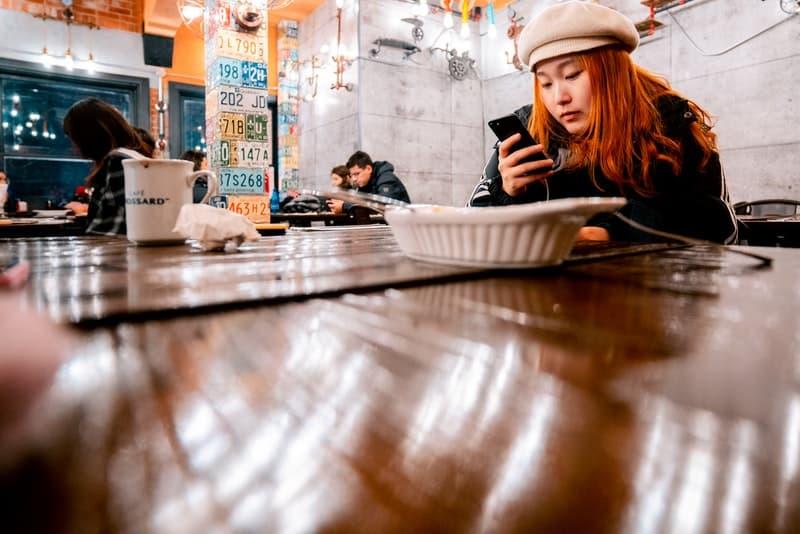Eine traurige Frau in einem Restaurant benutzt ein Smartphone