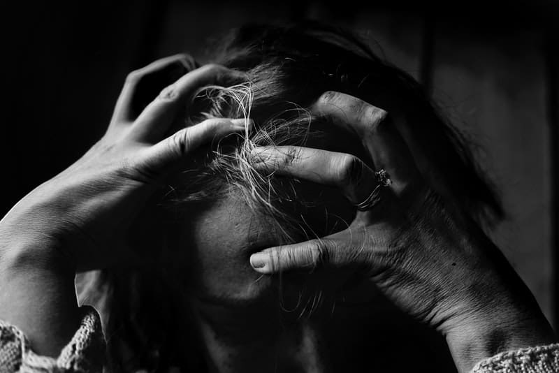 Eine traurige traumatisierte Frau hält den Kopf gesenkt