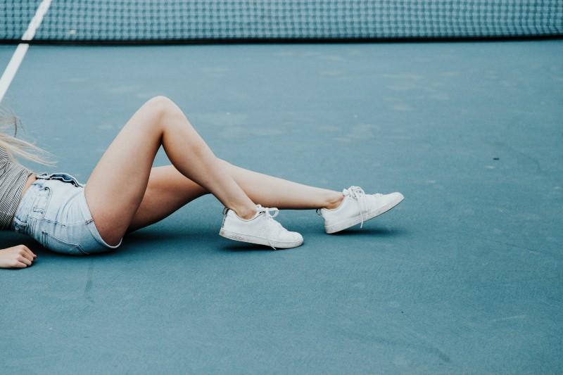 Frau, die tagsüber auf Tennisplatzboden liegt