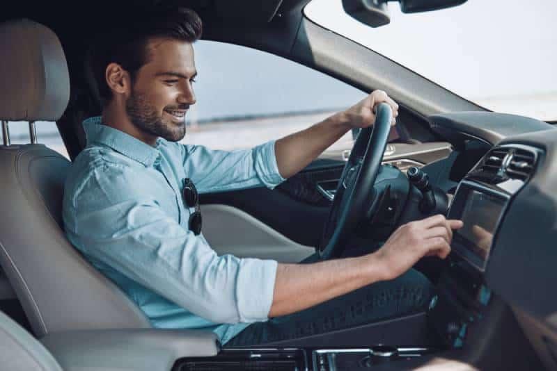 Hübscher junger Mann in der intelligenten Freizeitkleidung, die beim Fahren eines Statusautos lächelt