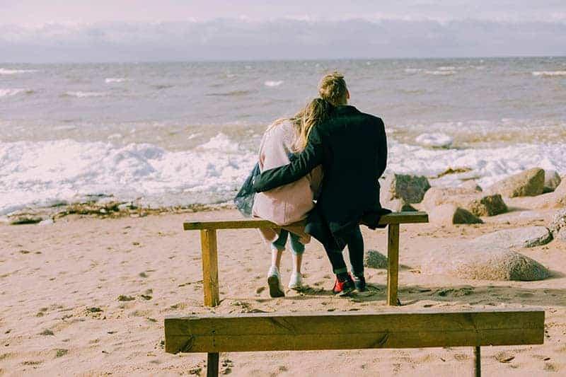 Mann, der Frau beim Sitzen am Strand umarmt