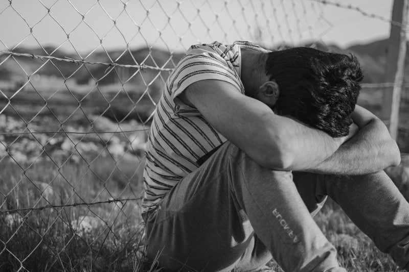 Mann im Schwarzweiss-Streifen-T-Shirt, das auf Maschendrahtzaun lehnt