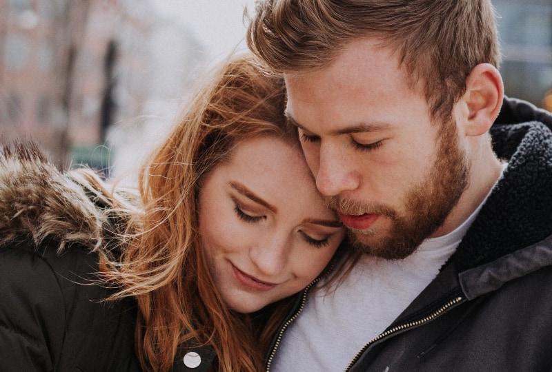 Mann umarmt Frau, die auf Straße steht