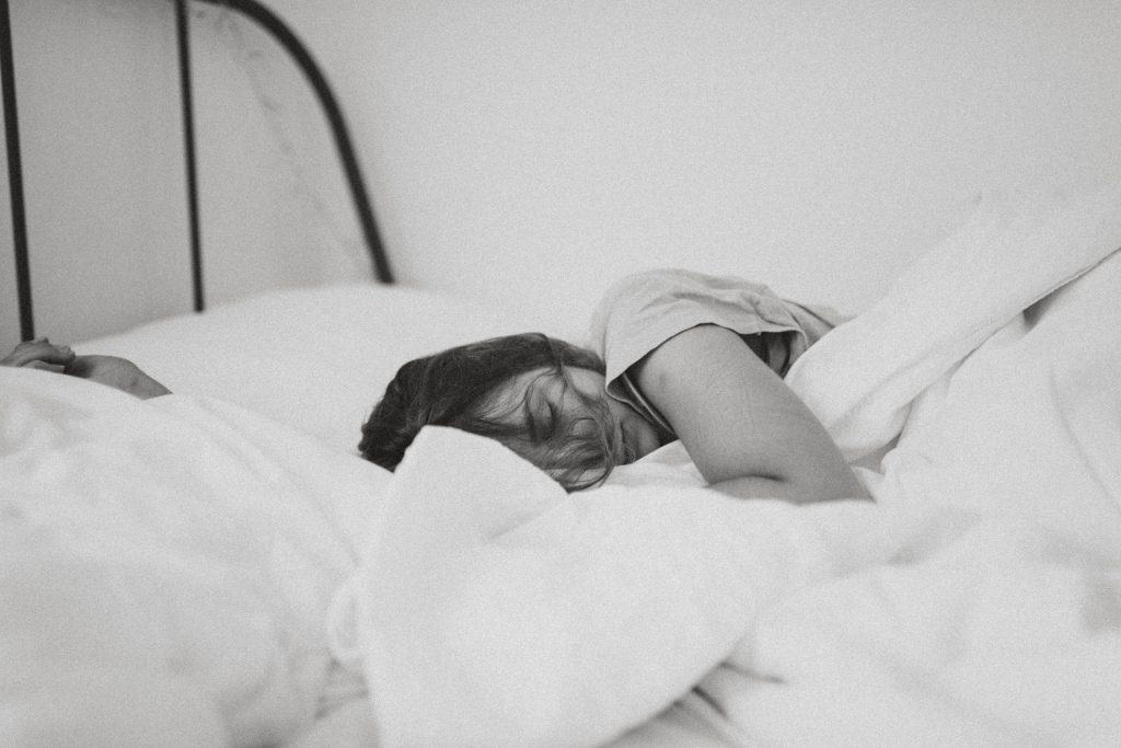 traurige Frau auf dem Bett liegen