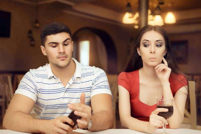 Neugieriges Mädchen, das Freund auf Smartphone ausspioniert