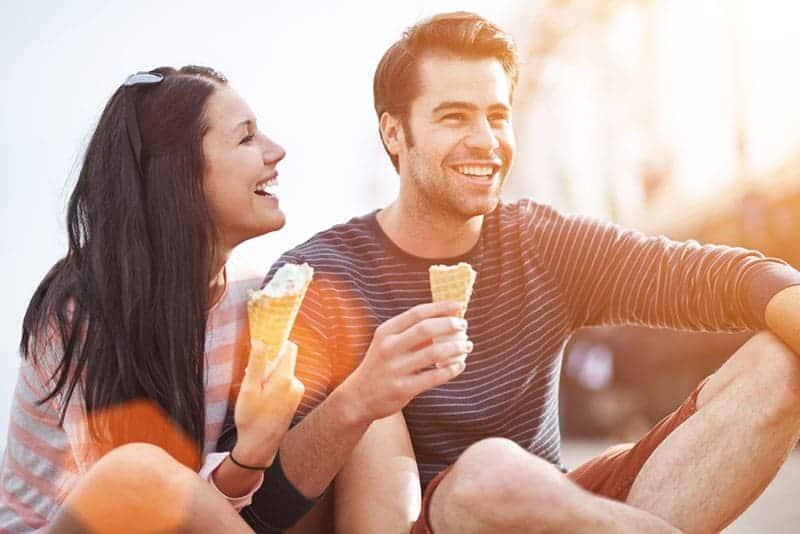 Paar lacht und isst Eis