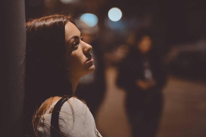 Porträt der nachdenklichen Frau, die gegen Straße lehnt