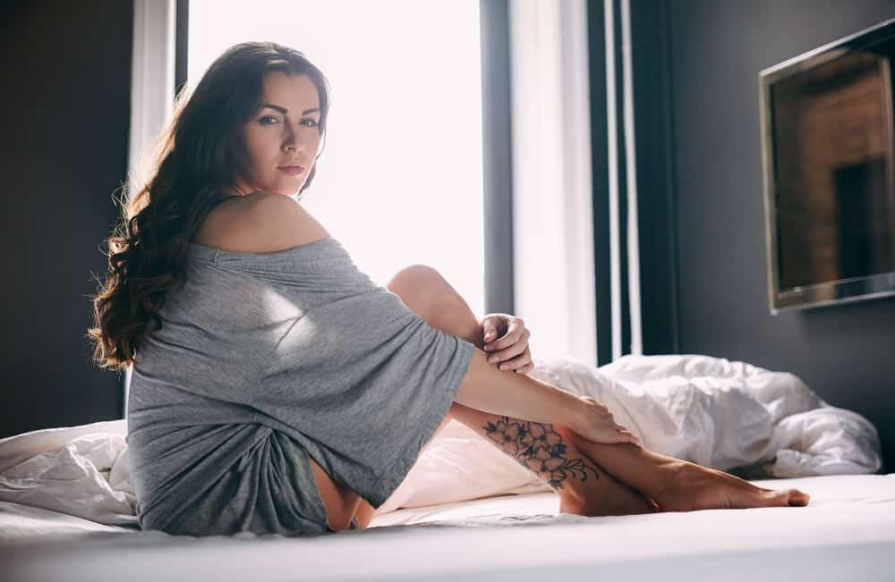 Porträt einer Brünetten mit einem Tattoo auf ihrem Bein, das auf dem Bett sitzt