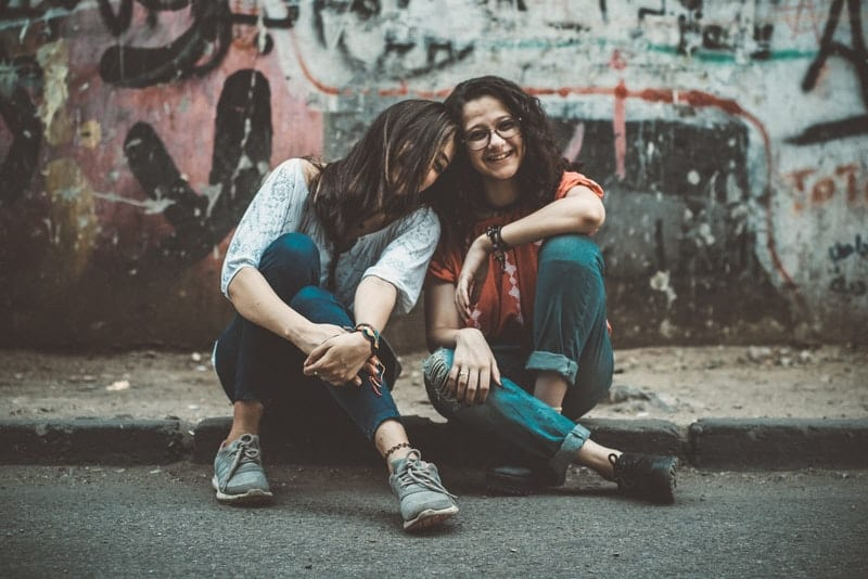 Zwei Freunde sitzen auf dem Bürgersteig und lehnen sich aneinander