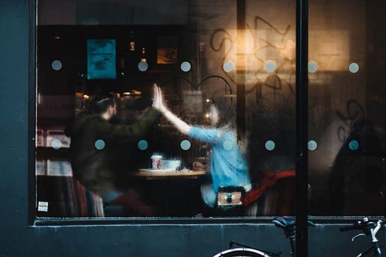 Zwei junge Leute sitzen in einem Café und werfen einen Knochen