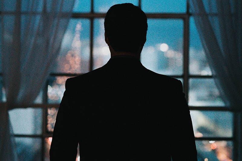 der Hintergrund eines Mannes, der aus einem Fenster schaut