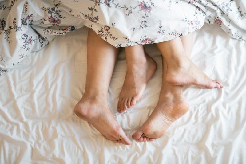 die Beine eines Mannes und einer Frau unter einer Decke(1)