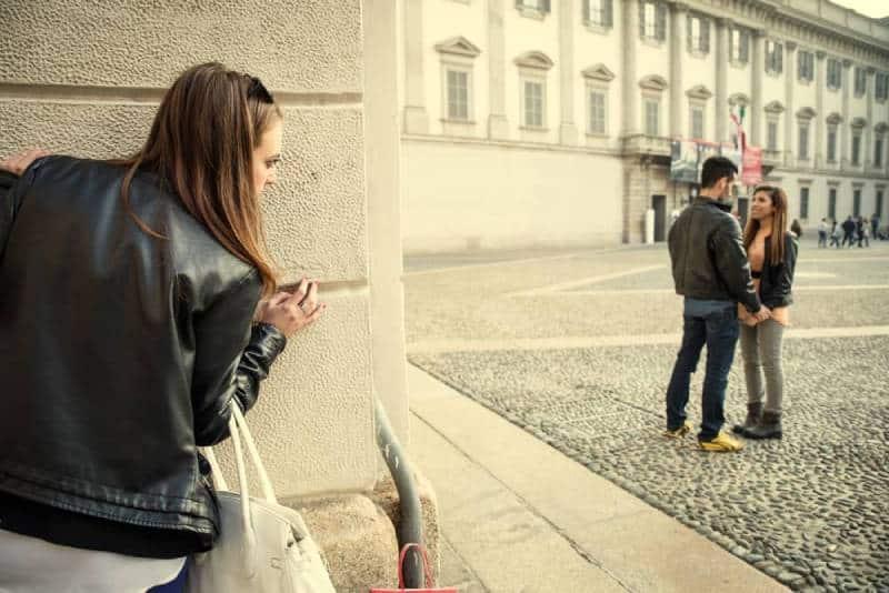 eifersüchtige Frau, die Paar auf Straße ansieht