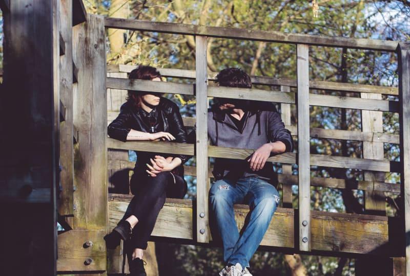 ein Paar spricht auf einer Holzbrücke