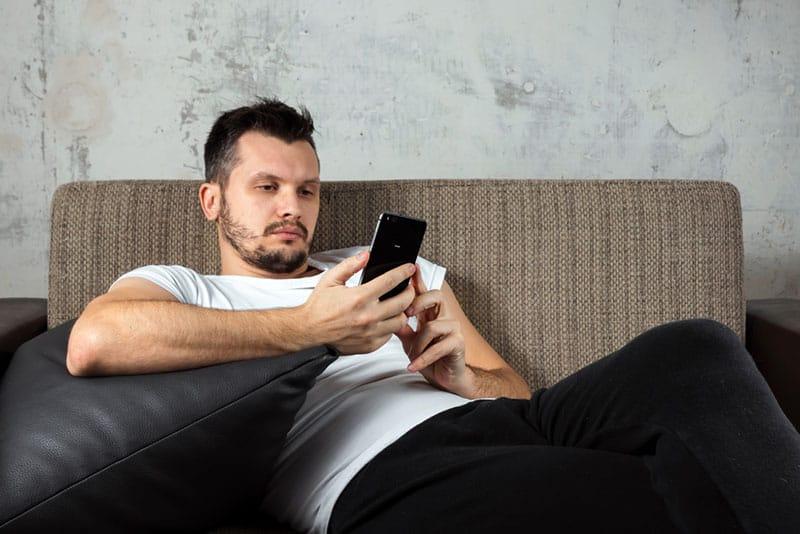fauler Mann sitzt auf der Couch und tippt