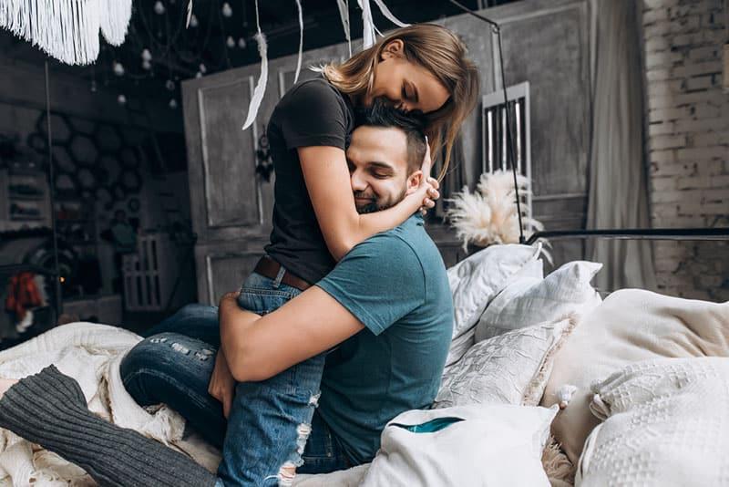 glückliches Paar, das auf dem Bett umarmt