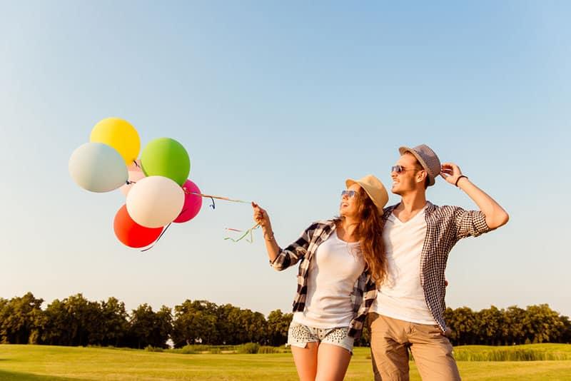 glückliches Paar, das mit Luftballons geht