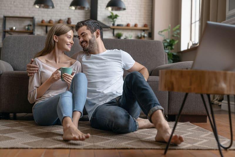 glückliches Paar sitzt auf dem Boden