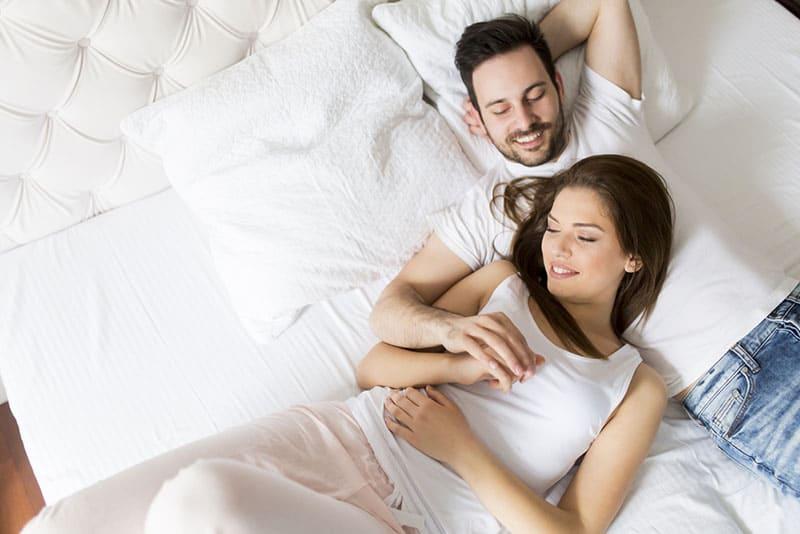 glückliches junges Paar, das auf dem Bett liegt