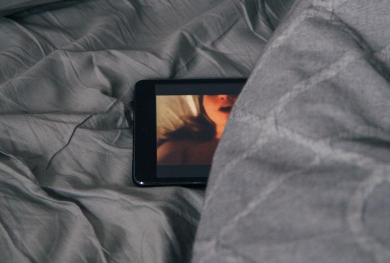 schwarzes Android-Smartphone auf grauem Bettlaken