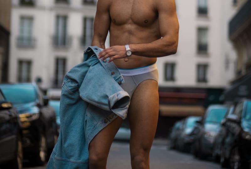 topless Mann in blauen Jeansshorts, die auf grauem Felsen sitzen