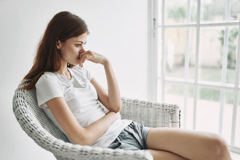 traurige besorgte Frau, die auf dem Stuhl sitzt