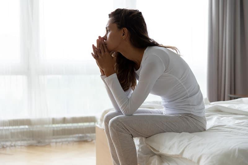 traurige einsame Frau, die auf dem Bett sitzt