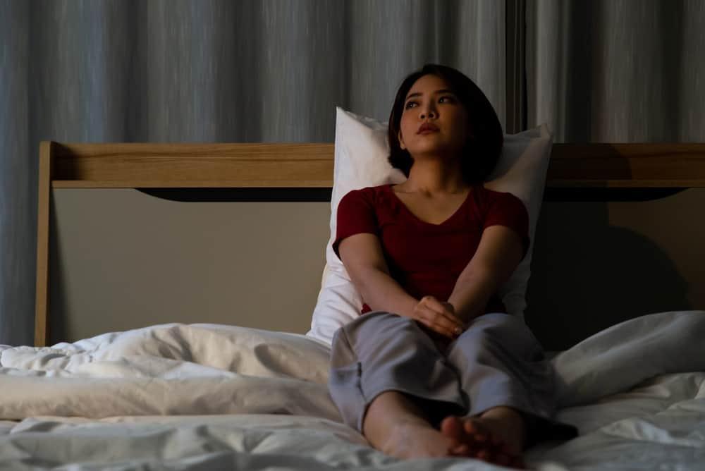traurige nachdenkliche Frau, die im Schlafzimmerbett sitzt