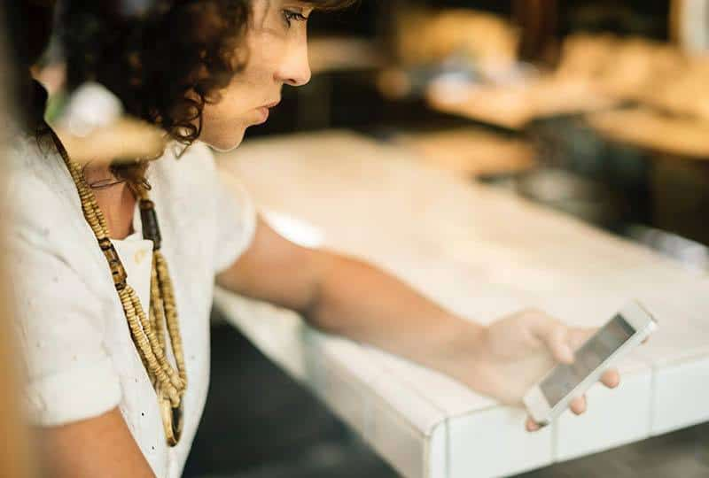 verzweifelte Frau, die ihr Telefon im Café betrachtet