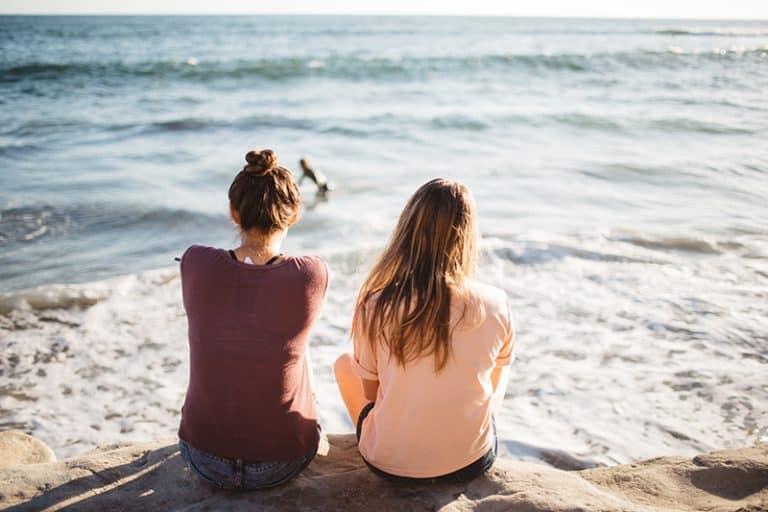 zwei junge Mädchen sitzen am Meer