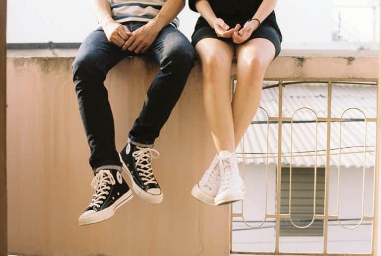 zwei junge Männer sitzen an der Wand und reden