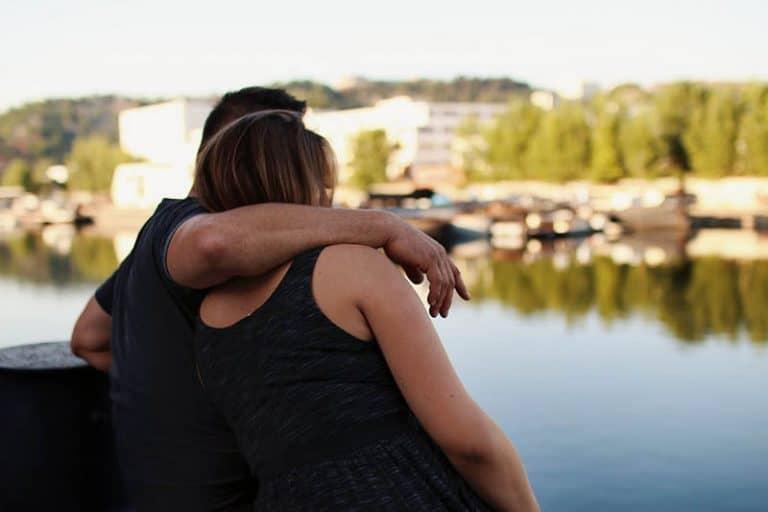 Mann, der Frau nahe See umarmt