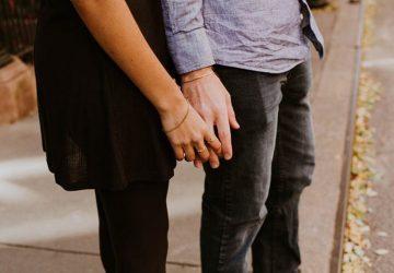 ein Paar auf der Straße stehen und Hände halten