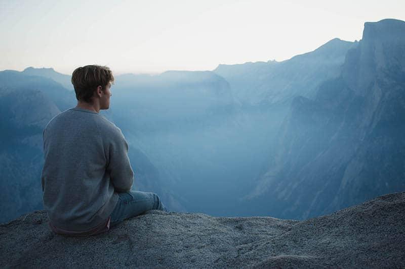 Ein Mann sitzt auf einem Felsen und schaut auf die Landschaft