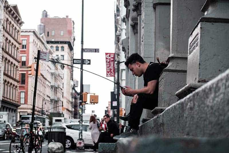 Mann, der eine Nachricht tippt, während er auf Betontreppen sitzt